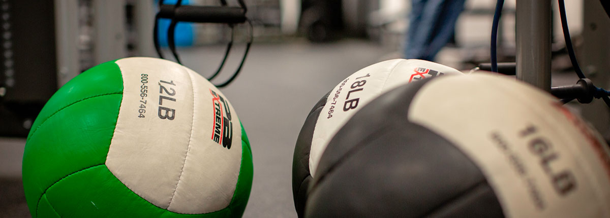 Close up photo of three different medicine balls resting on the weight room floor. Exercise equipment appears in the background.