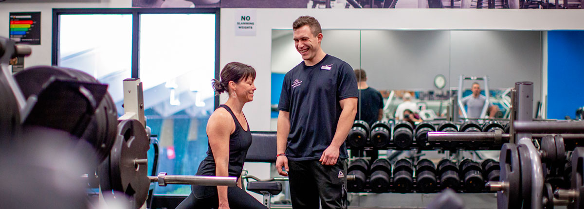 A male personal trainer stands above a female client, who holds a lunge position. Both are smiling.