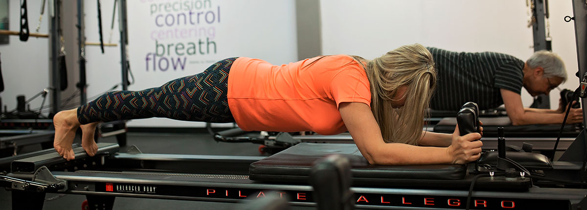 Photo of two members doing pilates reformer.
