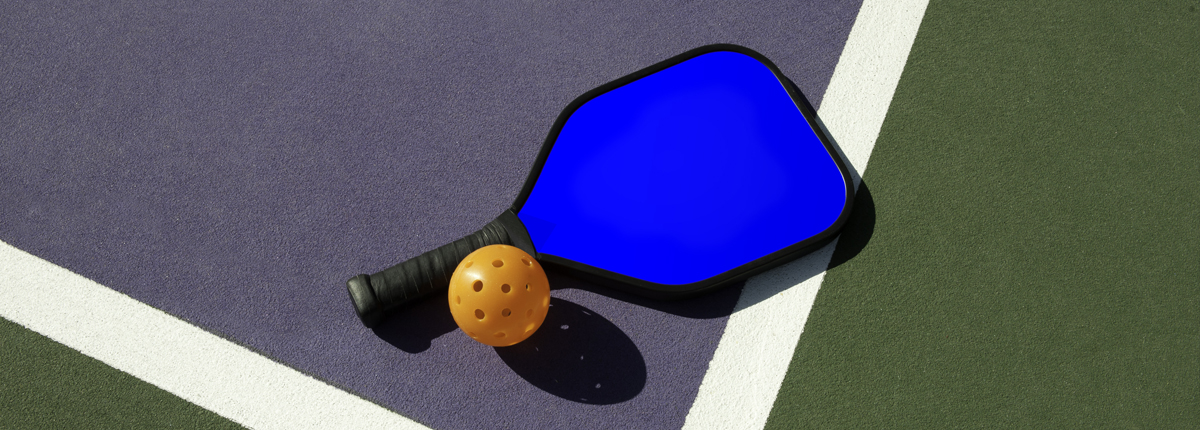 Pickleball at West Hills Athletic Club: A bright-blue pickleball racquet and orange pickleball rest on a pickleball court.