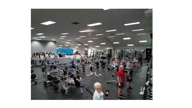 A wide angle view of the fitness floor, showing several patrons using the equipment.