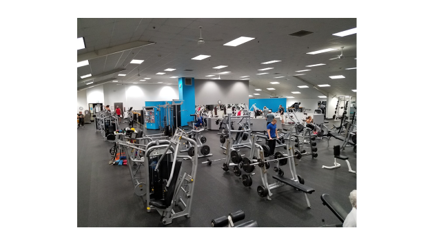A long view of the fitness floor, showing several patrons using the equipment.