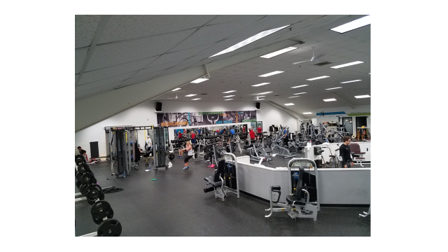 A side view of the fitness floor, showing several patrons using the equipment.