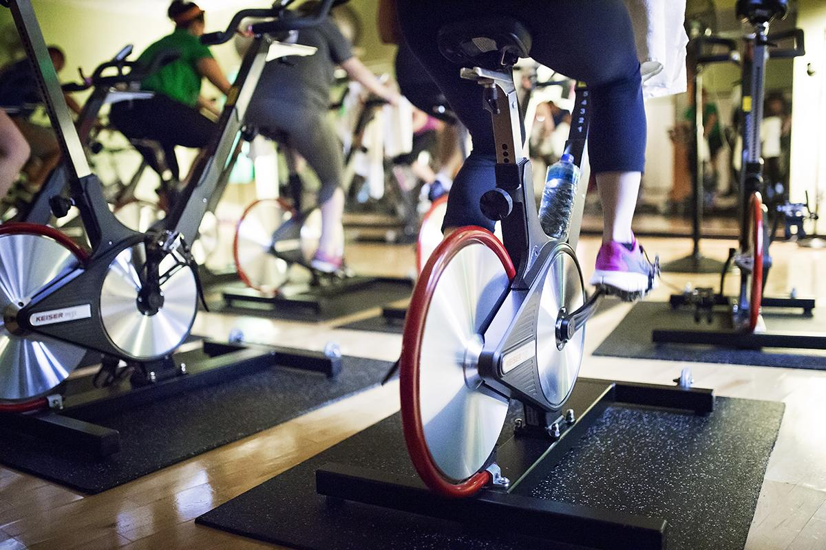 A spin class in session, as seen from behind the patrons.