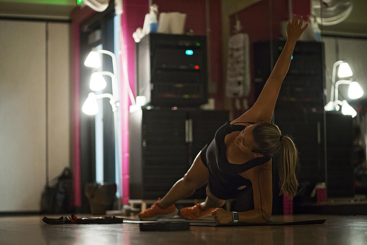 A female patron performs a side plank.