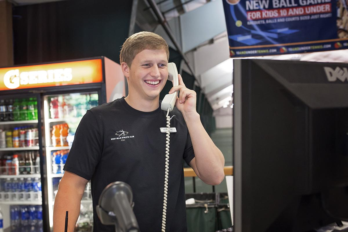 A smiling male West Hills employee answers the phone.