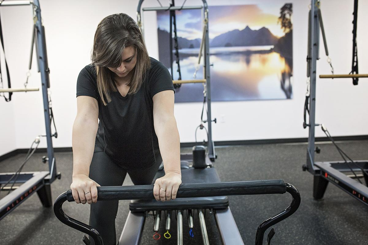 A woman uses Pilates equipment at West Hills Athletic Club.