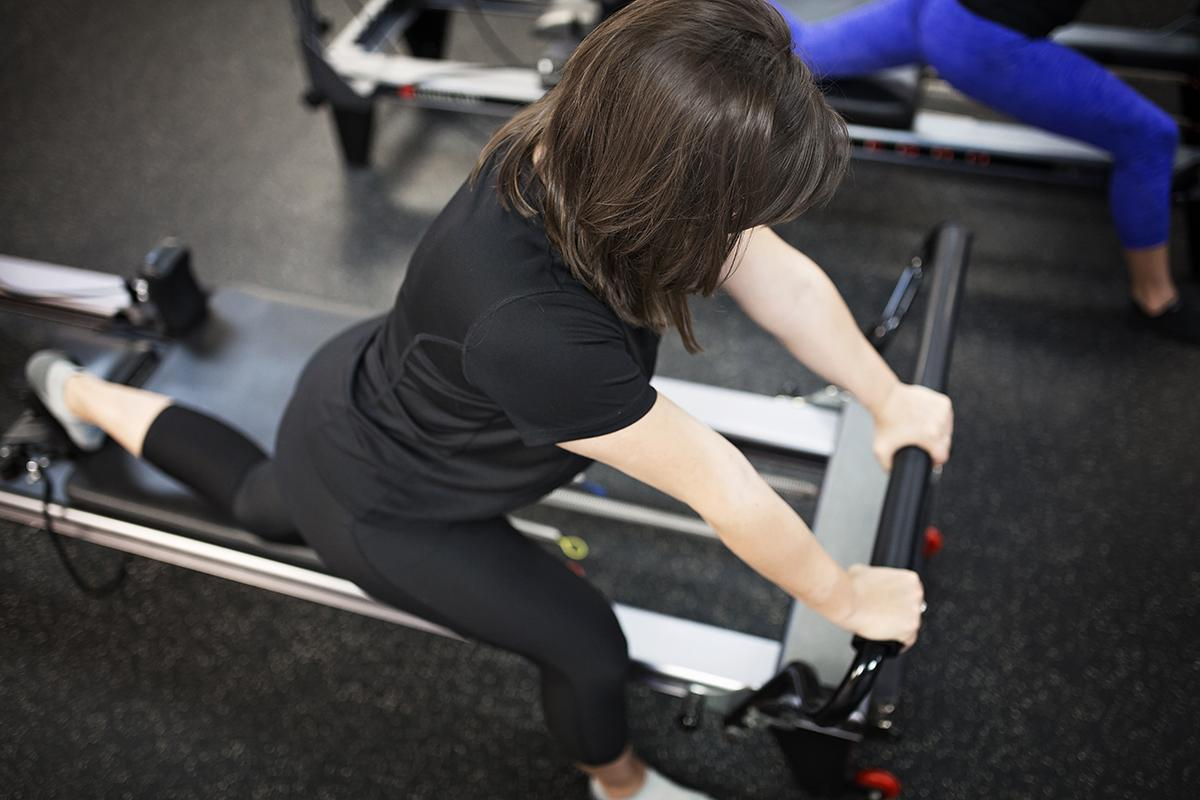 A woman stretches on Pilates equipment at West Hills Athletic Club.