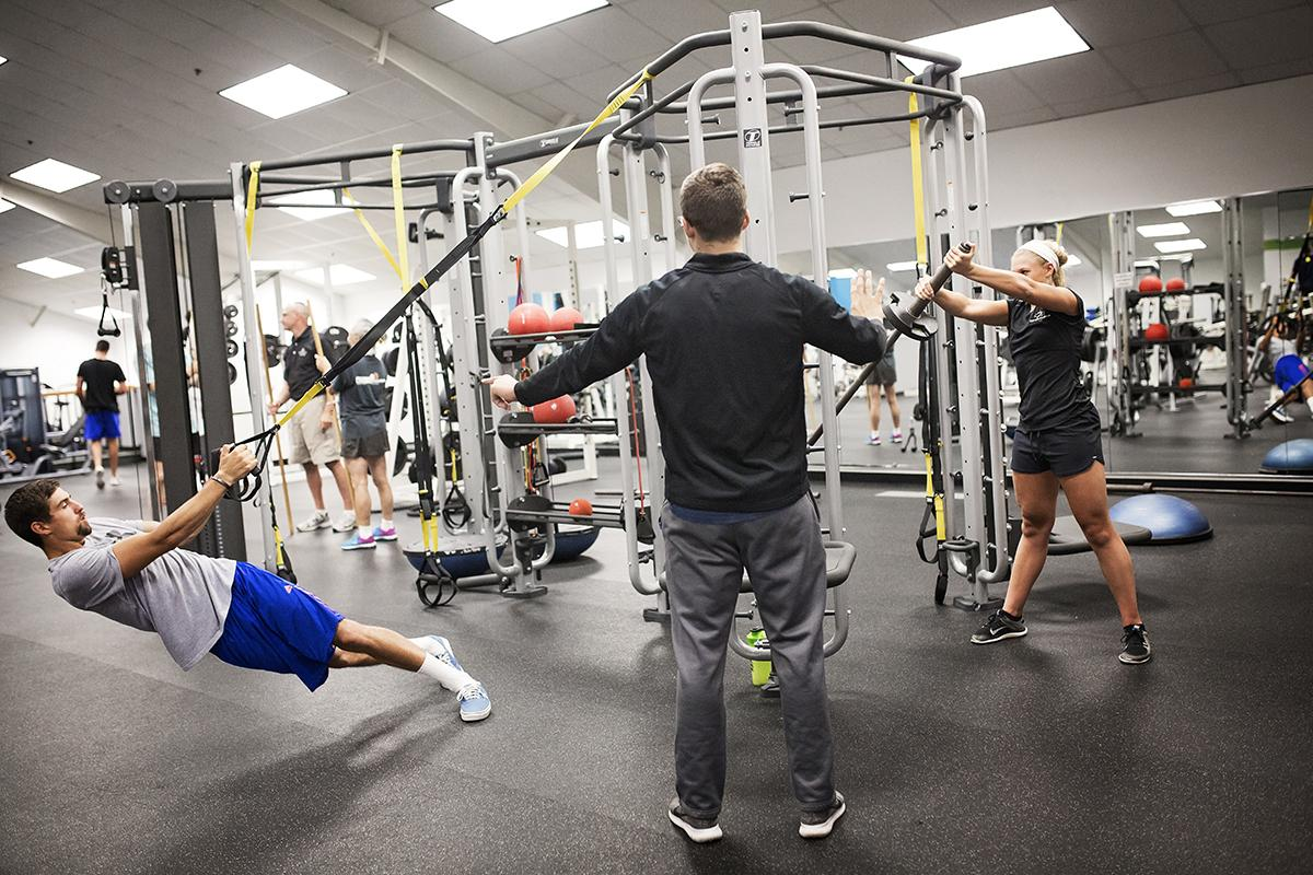 A trainer instructs two health club patrons as they use the health club equipment.