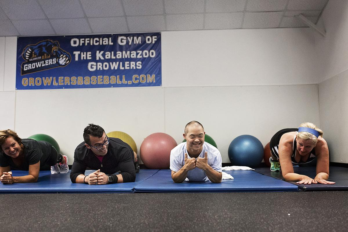 Four health club members hold planks and look at the camera.