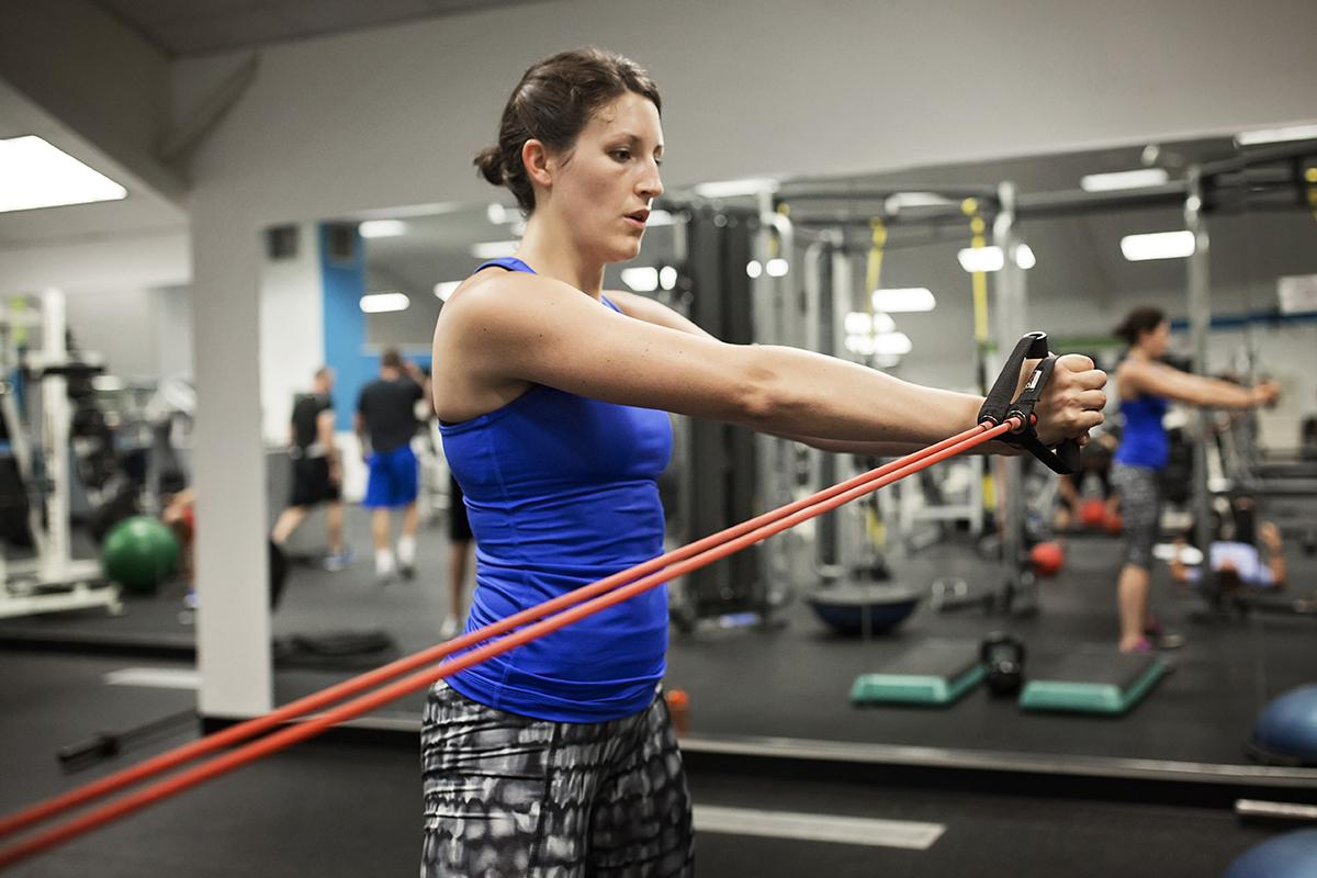 A female patron pulls on resistance bands.