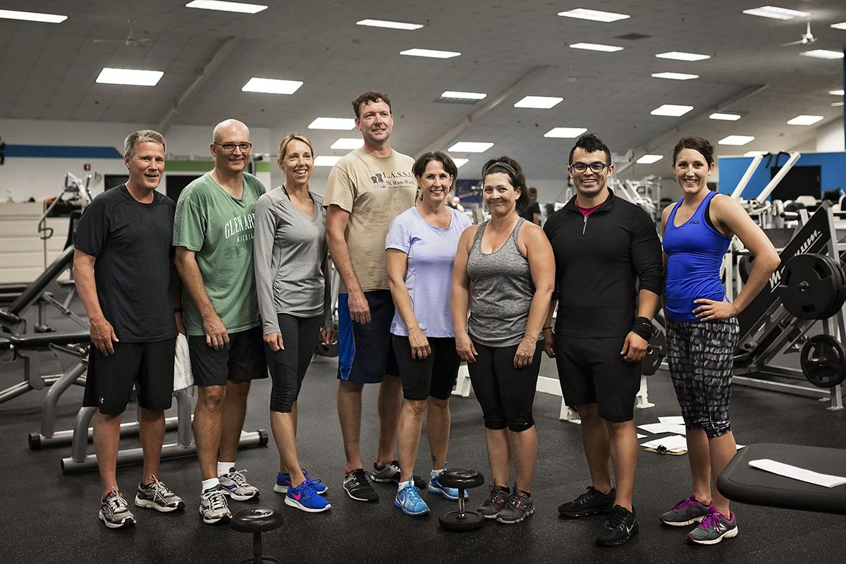 A group of patrons and trainers stands together, smiling at the camera.