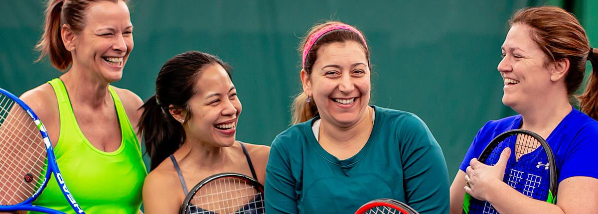 Group of ladies holding tennis rackets looking at each other and smiling.
