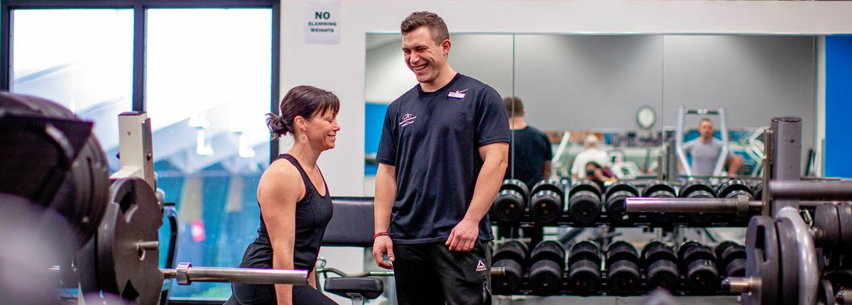 A male personal trainer works with a female client. They stand in a well-lit room in front of a rack of free weights.
