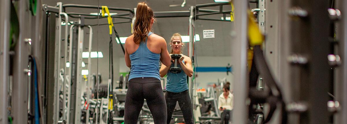 Seen from behind, woman in a tank top stands in front of a mirror, performing a goblet squat with a dumbbell.